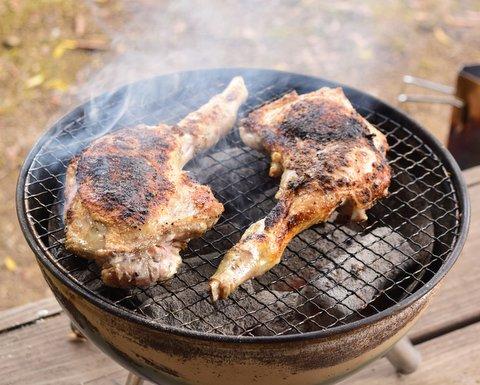 骨付き鶏モモ肉を炭火で焼く