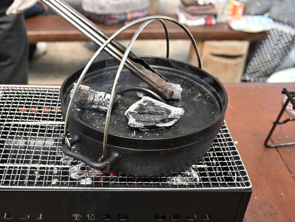 ダッチオーブンの上下から炭火で焼く