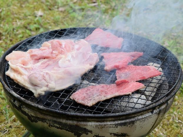 炭火で鶏肉と牛肉を焼く