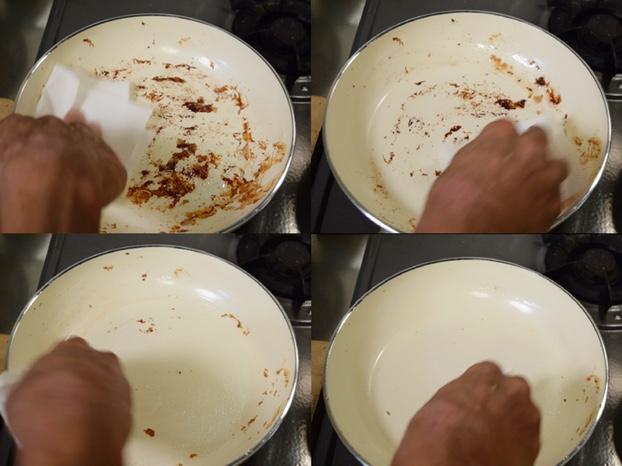 キッチンペーパーでフライパンの汚れを拭き取る