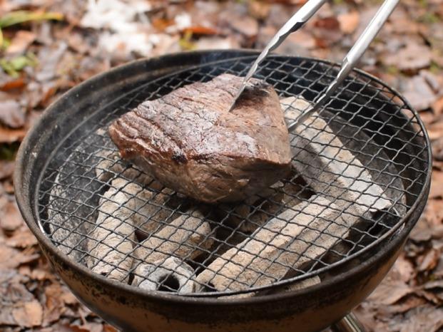 牛肉の塊を炭火で焼く