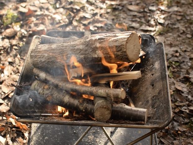 焚き火に太い薪を入れて燃やす