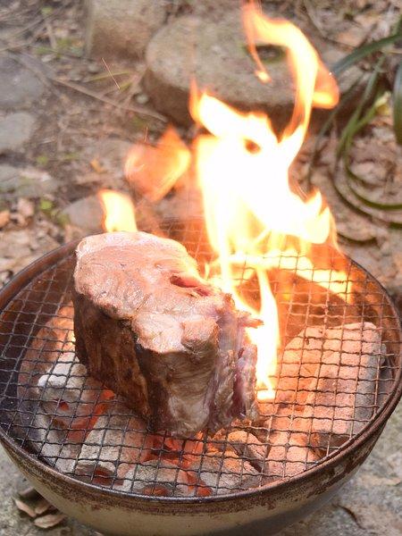 豚肉を炭火で焼き炎があがる