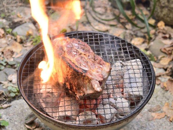 豚肉を炭火で焼く炎があがる