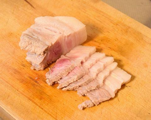 茹でた豚ばら肉をスライスする
