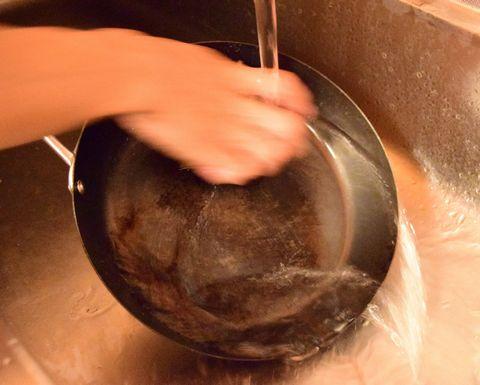たわしでフライパンを洗う