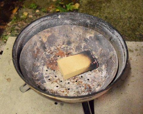 蓋付きバーベキューコンロに火の付いたスモークウッドを置く