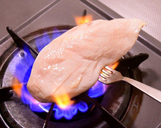 サラダチキンにフォークを刺してガスコンロで焼く